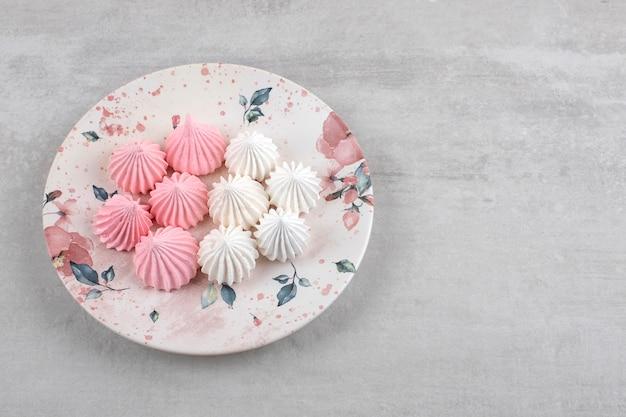 Merengue rosa e branco em um prato, na mesa de mármore.