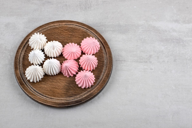 Merengue rosa e branco em uma placa, na mesa de mármore.