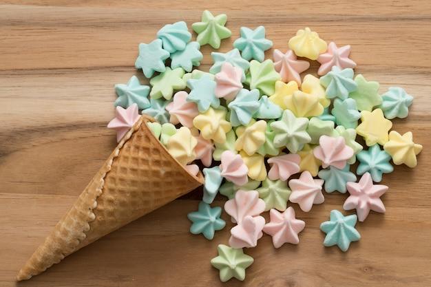 Merengues da cor dos doces no cone de gelado. fundo de madeira