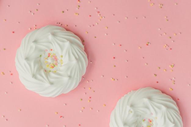 Merengues de ar branco caseiro e decorações de confeitaria em rosa