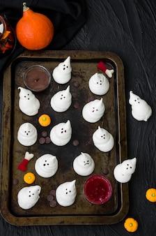 Merengues de halloween dos fantasmas com molhos do chocolate e da baga em uma assadeira velha em um fundo preto. ideia de comida para festa de halloween.