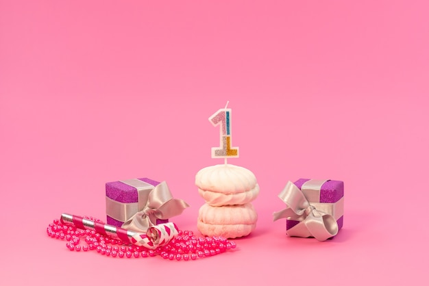 Merengues de vista frontal e caixas em rosa, bolo de aniversário