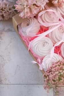 Merengues em caixa de presente e flores cor de rosa