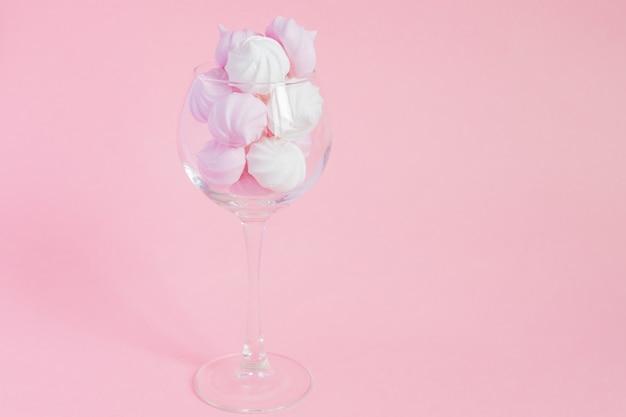 Merengues torcidos brancos e rosa em um copo de videira em rosa