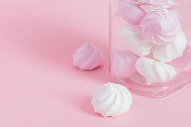 Merengues torcidos brancos e rosa em uma jarra de vidro rosa