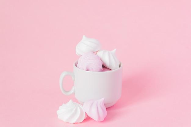 Merengues torcidos brancos e rosa em uma xícara de café de porcelana pequena em fundo rosa. sobremesa francesa preparada a partir de chantilly com açúcar e claras de ovos cozidas. cartão com espaço de cópia