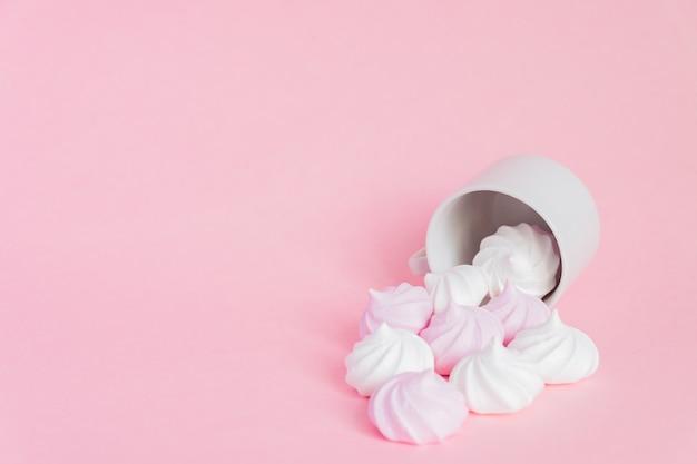 Merengues torcidos brancos e rosa em uma xícara de café de porcelana pequena em fundo rosa.