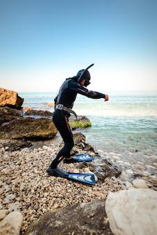 Mergulhador em pé na praia