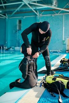 Mergulhador feminino e masculino experimentando equipamento de mergulho