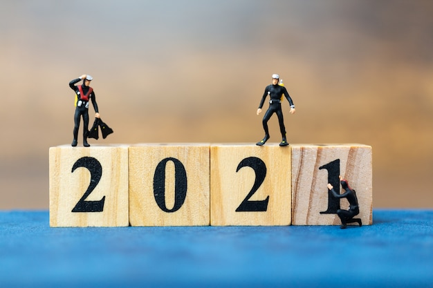 Mergulhadores de pessoas em miniatura mergulhando em torno de um bloco de madeira 2021, conceito de feliz ano novo
