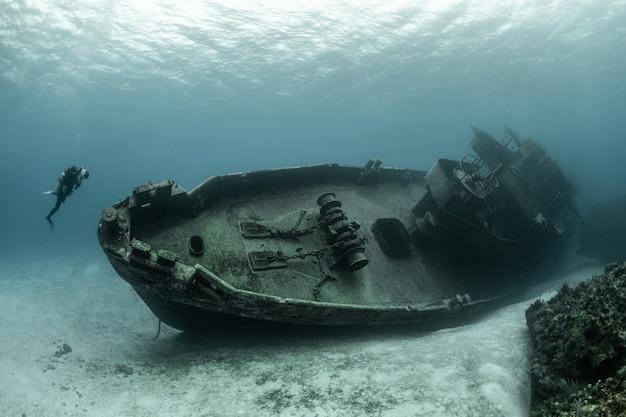 Mergulhadores examinando o famoso naufrágio do submarino uss kittiwake nas ilhas grand cayman