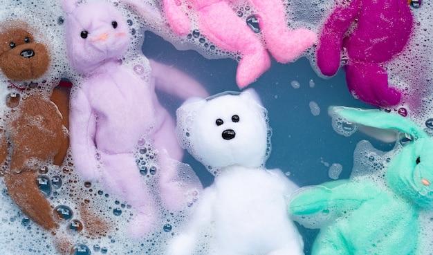 Mergulhe a boneca coelho com ursinho de brinquedo na dissolução da água do detergente antes de lavar. conceito de lavanderia