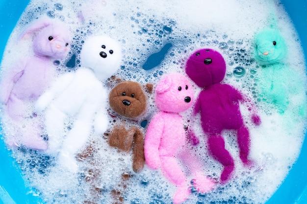 Mergulhe as bonecas de coelho com brinquedos de urso na dissolução da água do detergente antes de lavar. conceito de lavanderia