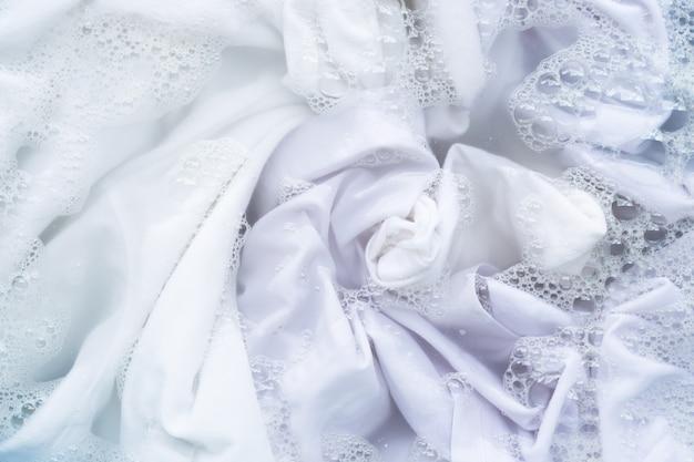 Mergulhe as roupas brancas na dissolução da água com detergente em pó. conceito de lavanderia
