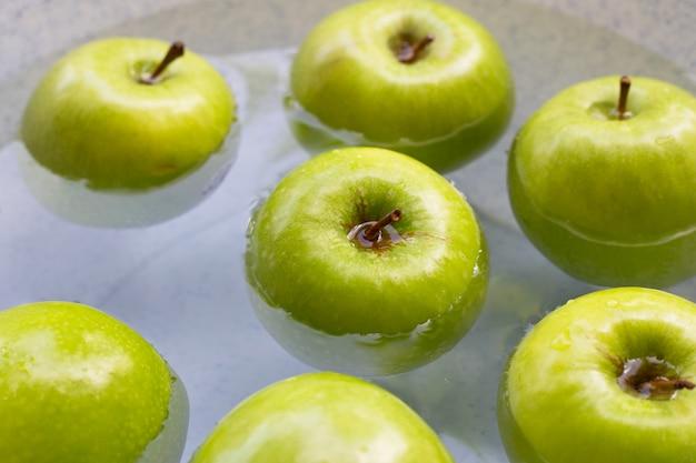 Mergulhe maçãs verdes em água. conceito de lavagem de frutas