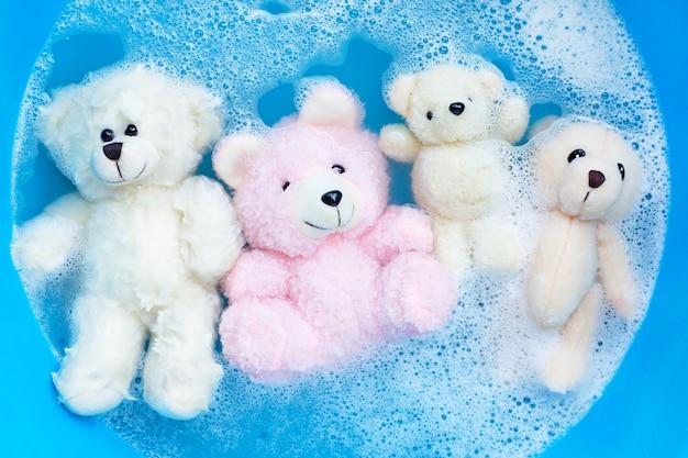 Mergulhe os ursos de brinquedo na dissolução da água do detergente antes de lavar. lavar roupa,