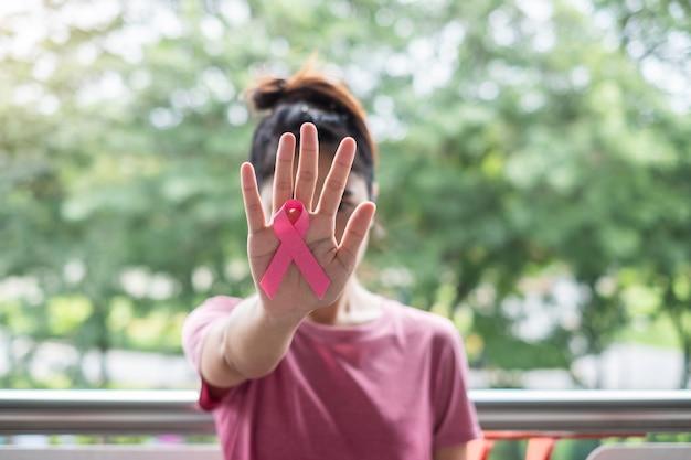 Mês de conscientização do câncer de mama de outubro, mulher de camiseta rosa com a mão segurando a fita rosa para apoiar as pessoas que vivem e doenças. cuidados de saúde, dia internacional da mulher e conceito do dia mundial do câncer