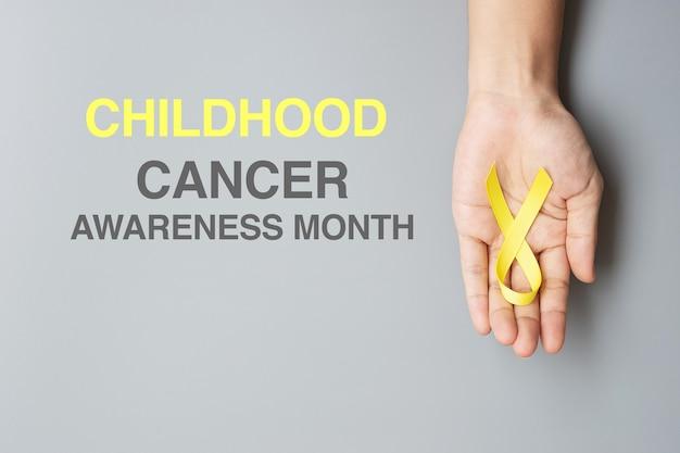 Mês de conscientização do câncer na infância, mão segurando a fita amarela dourada para apoiar as pessoas que vivem e estão doentes. conceito de saúde infantil e dia mundial do câncer