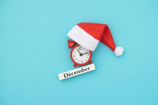 Mês de dezembro, despertador vermelho e chapéu de papai noel