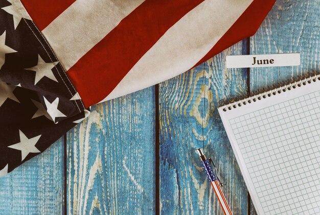 Mês de junho do ano civil estados unidos da américa bandeira do símbolo da liberdade e da democracia com o bloco de notas em branco e caneta na mesa de escritório de madeira