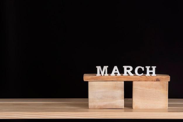 Mês de março de blocos de madeira na prateleira de madeira