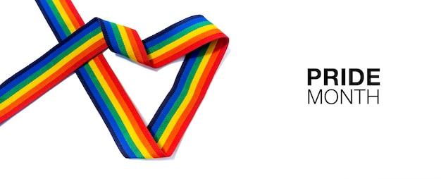Mês do orgulho com fita de listra de arco-íris de forma de coração isolada no fundo branco. conceito lgbt com cores do orgulho e faixa da bandeira do arco-íris. fundo de banner lgbt.