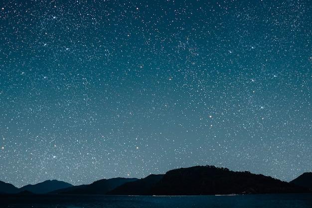 Mês em um céu estrelado de superfície refletido no mar.