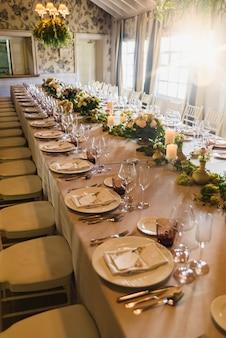 Mesa alongada com todos os talheres elegantemente arranjados e belas peças centrais