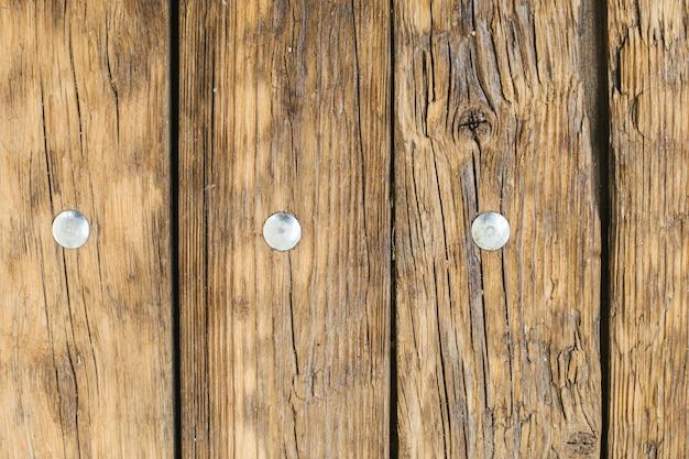 Mesa antiga de madeira leve natural com textura de pregos de ferro