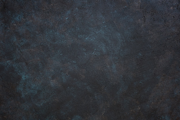 Mesa áspera escura texturizada com manchas azuis e amarelas