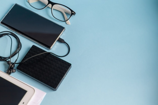 Mesa azul clara com os itens necessários. diário com caneta, telefone samsung. branca xícara de café.