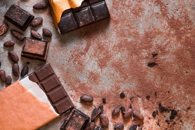 Mesa bagunçada com grãos de cacau e barra de chocolate e pedaços na mesa rústica