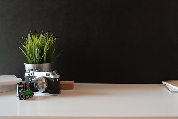 Mesa branca com câmera vintage e espaço de cópia