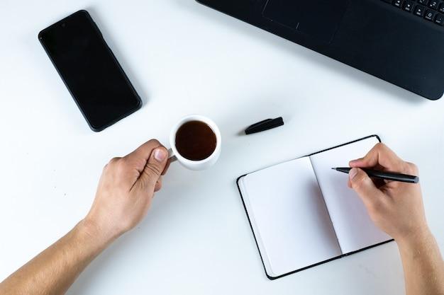 Mesa branca com computador, mãos, celular, caneta, chá e caderno de cima. conceito pronto para trabalhar