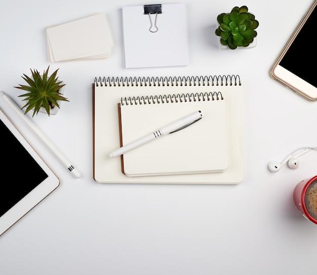 Mesa branca com tablet eletrônico, smartphone, cartões de visita em branco, xícara de café