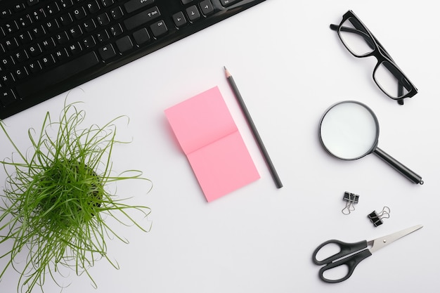 Mesa branca com teclado, óculos, lupa, adesivos rosa, clipes, tesoura, planta de escritório e lápis.
