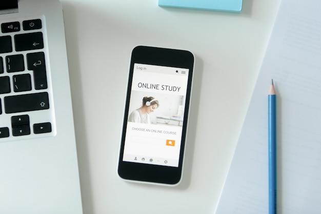 Mesa branca com um telefone celular com estudo em linha do título