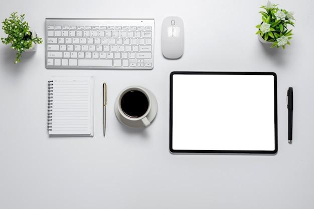 Mesa branca de vista superior com notebook de mouse teclado de café de tela branca de tablet em uma mesa branca.