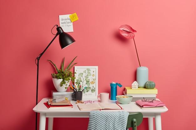 Mesa branca do aluno com lâmpada, caderno aberto, livros, garrafa térmica de café e lírios rosados em um vaso