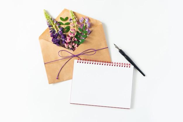 Mesa branca encontra-se um envelope, caderno, caneta e flores