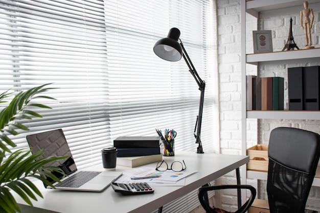Mesa branca moderna perto da janela no escritório com espaço de cópia.