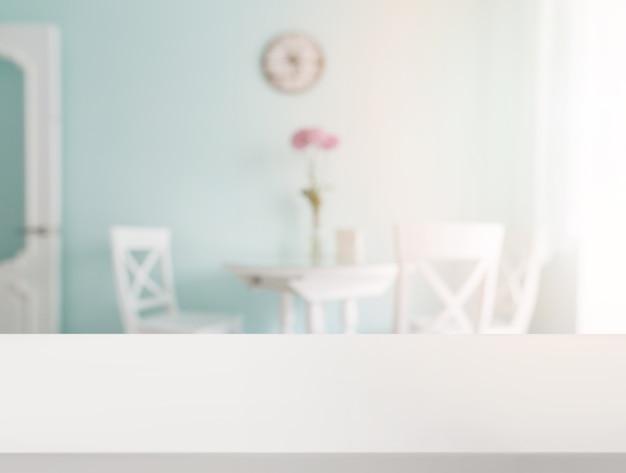 Mesa branca vazia na frente da mesa de jantar branca turva na casa