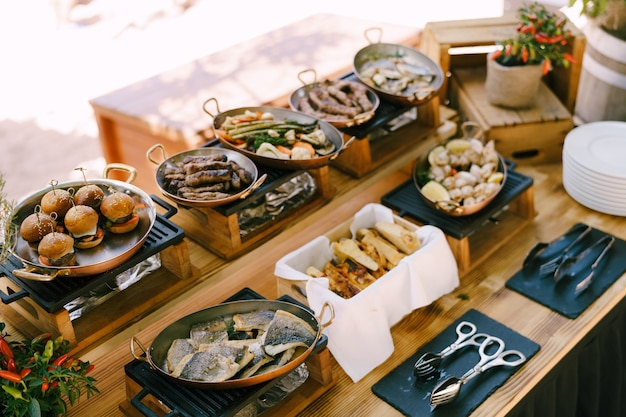 Mesa buffet com frigideiras de cobre e pratos preparados para a festa de peixe frito em frigideira mini