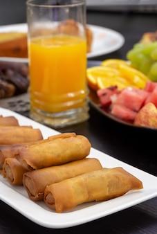 Mesa buffet iftar. rolinho primavera, frutas frescas, suco de laranja, lanche samosa, rolinho primavera e frutas