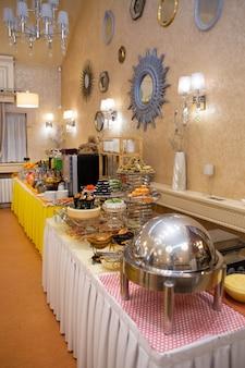 Mesa buffet no hotel com vários pratos.