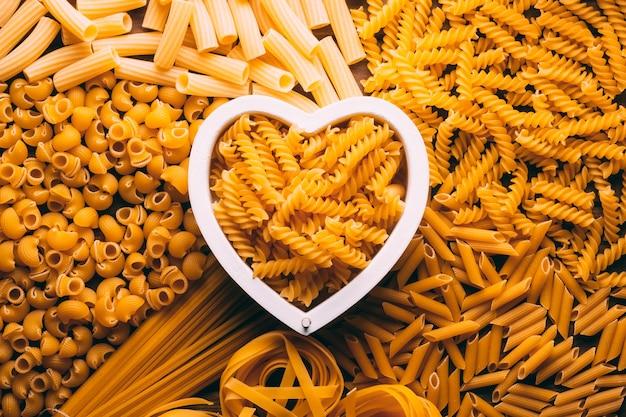 Mesa cheia de diferentes tipos de massas com formato de coração no centro, amantes das massas