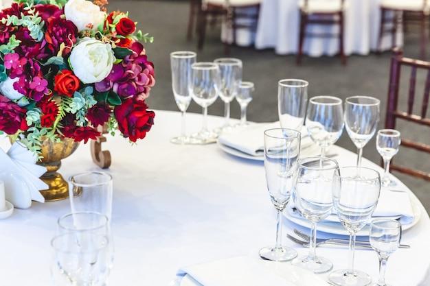 Mesa chique posta para jantar com composição de flores em restaurante, interior luxuoso