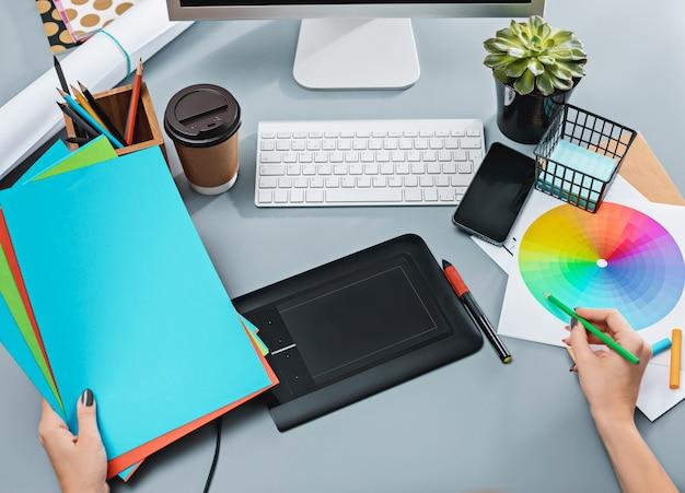 Mesa cinza com laptop, bloco de notas com uma folha em branco, vaso de flores, caneta e tablet para retoque