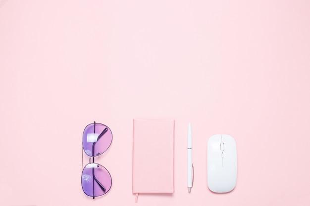Mesa colorida rosa com diário colorido rosa, caneta branca, mouse branco e óculos de sol roxos. composição plana leiga minimalista