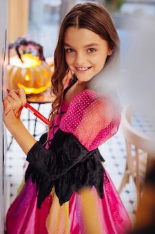 Mesa com abóbora. menina feliz de cabelos escuros radiante com vestido rosa e preto de halloween em pé perto da mesa com abóbora